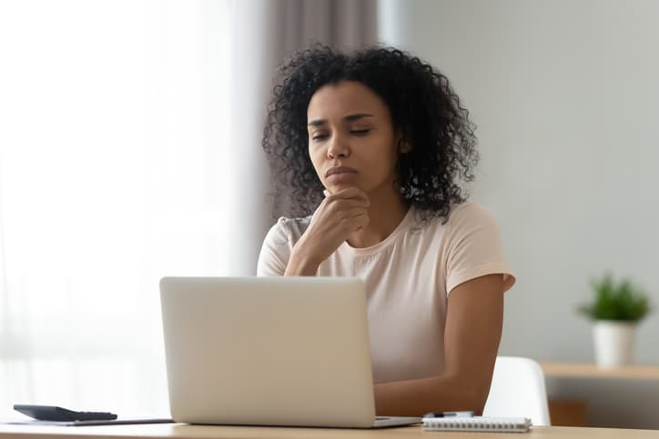 Pensive african American young woman sit at desk thinking studying or working on laptop at home, thoughtful black millennial girl student pondering considering idea looking at computer screen (Pensive african American young woman sit at desk thinking